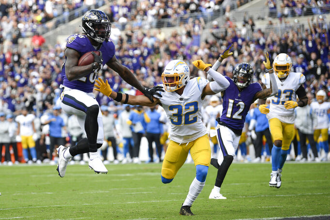 Baltimore Ravens running back Latavius Murray (28) scores a touchdown as Los Angeles Chargers defensive back Alohi Gilman (32) tries to stop him during the first half of an NFL football game, Sunday, Oct. 17, 2021, in Baltimore. (AP Photo/Nick Wass)
