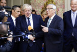 European Commission President Jean-Claude Juncker, center right, speaks with the media as he shakes hands with British Prime Minister Boris Johnson prior to a meeting at a restaurant in Luxembourg, Monday, Sept. 16, 2019. British Prime Minister Boris Johnson was holding his first meeting with European Commission President Jean-Claude Juncker on Monday in search of a longshot Brexit deal. (AP Photo/Olivier Matthys)