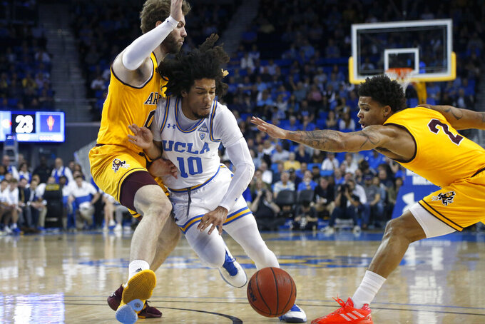 UCLA guard Tyger Campbell (10) drives between Arizona State forward Mickey Mitchell, left, and guard Rob Edwards (2) during an NCAA college basketball game Thursday, Feb. 27, 2020, in Los Angeles. (AP Photo/Ringo H.W. Chiu)