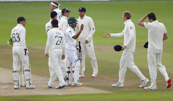 Pakistan's Babar Azam, center wearing helmet, greets England' players at the end of the fifth day of the third cricket Test match between England and Pakistan, at the Ageas Bowl in Southampton, England, Tuesday, Aug. 25, 2020. (AP Photo/Alastair Grant, Pool)