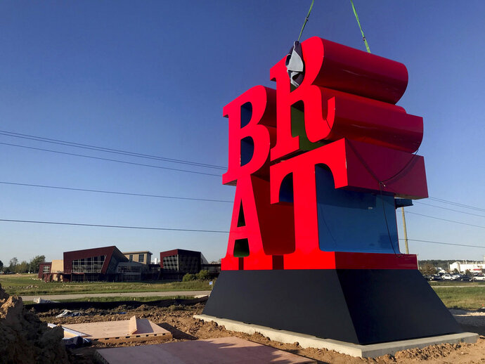 The letter R is lowered into place as Johnsonville Sausage installs one of Robert Indiana's last pieces of art ' a sculpture spelling out the word BRAT at its headquarters in Sheboygan Falls, Wis., on Tuesday, Sept. 11, 2018. It is the late Indiana's last monumental sculpture. A tribute to bratwurst, it was commissioned by the owners of Johnsonville Sausage. (Mike De Sisti /Milwaukee Journal-Sentinel via AP)