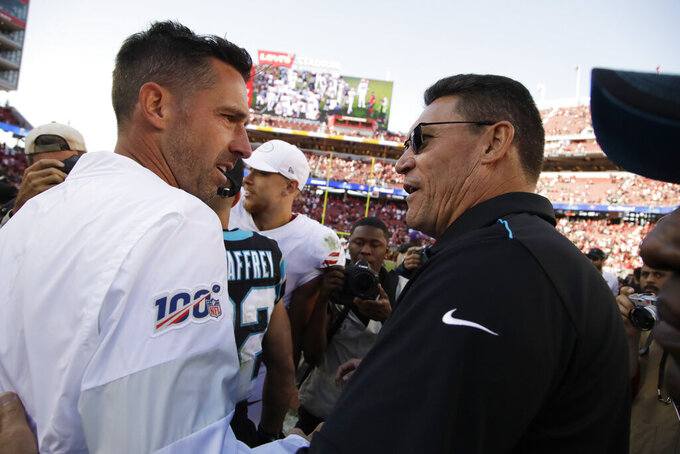 San Francisco 49ers head coach Kyle Shanahan, left, greets Carolina Panthers head coach Ron Rivera at the end of an NFL football game in Santa Clara, Calif., Sunday, Oct. 27, 2019. San Francisco won the game 51-13. (AP Photo/Ben Margot)