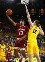 Indiana forward Juwan Morgan (13) shoots on Michigan center Jon Teske (15) in the first half of an NCAA college basketball game in Ann Arbor, Mich., Sunday, Jan. 6, 2019. (AP Photo/Paul Sancya)