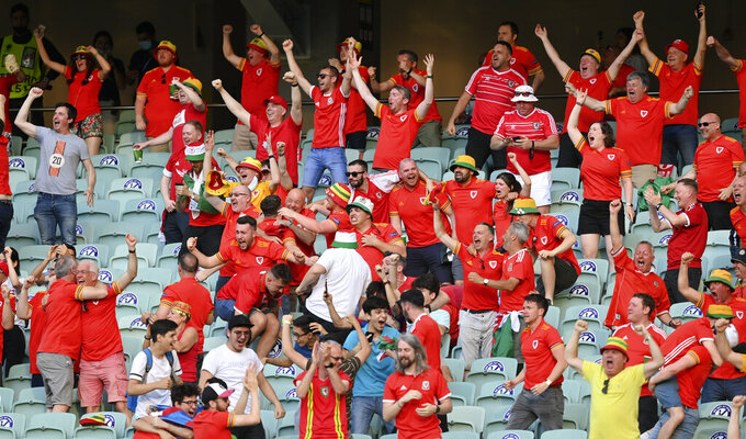 Welsh fans celebrate after their team's first goal during the Euro 2020 soccer championship group A match between Wales and Switzerland at Baku Olympic Stadium in Baku, Azerbaijan, Saturday, June 12, 2021. (AP Photo/Dan Mullan, Pool)