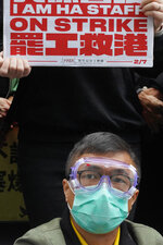Medical staff strike over coronavirus concerns outside government headquarters in Hong Kong, Wednesday, Feb. 5, 2020. In Hong Kong, hospitals workers are striking to demand the border with mainland China be shut completely to ward off the virus, but four new cases without known travel to the mainland indicate the illness is spreading locally in the territory.(AP Photo/Vincent Yu)