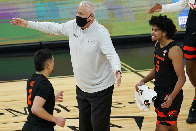 Oregon State head coach Wayne Tinkle speaks with players at a timeout during the first half of an NCAA college basketball game against Oregon in the semifinal round of the Pac-12 men's tournament Friday, March 12, 2021, in Las Vegas. (AP Photo/John Locher)