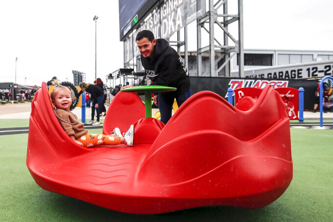 Nascar driver Kyle Larson spins his daughter Audrey as they explore the new facilities and garages at Talladega Superspeedway, Saturday, Oct. 12, 2019, in Talladega, Ala. (AP Photo/Butch Dill)