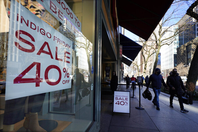 FILE - In this Saturday, Nov. 28, 2020 file photo, shoppers pass an Indigo Friday 40% Off sign on Chicago's famed Magnificent Mile shopping district. Retail sales rose 5.1% in November, as spending on home furnishings and electronics helped offset a drop in sales of clothing and at department stores, according to figures released Thursday, Dec. 3 by Mastercard SpendingPulse. (AP Photo/Charles Rex Arbogast, File)
