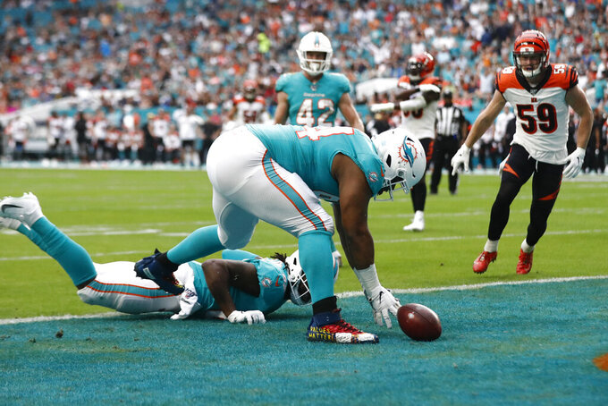 Miami Dolphins defensive tackle Christian Wilkins (94) fumbles and recovers the football after scoring a touchdown, during the first half at an NFL football game against the Cincinnati Bengals, Sunday, Dec. 22, 2019, in Miami Gardens, Fla. (AP Photo/Brynn Anderson)