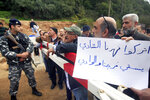 Lebanese protesters hold a placard in Arabic that reads: