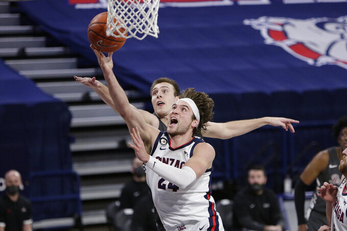 Gonzaga forward Corey Kispert, front, shoots in front of Santa Clara forward Josip Vrankic during the second half of an NCAA college basketball game in Spokane, Wash., Thursday, Feb. 25, 2021. (AP Photo/Young Kwak)