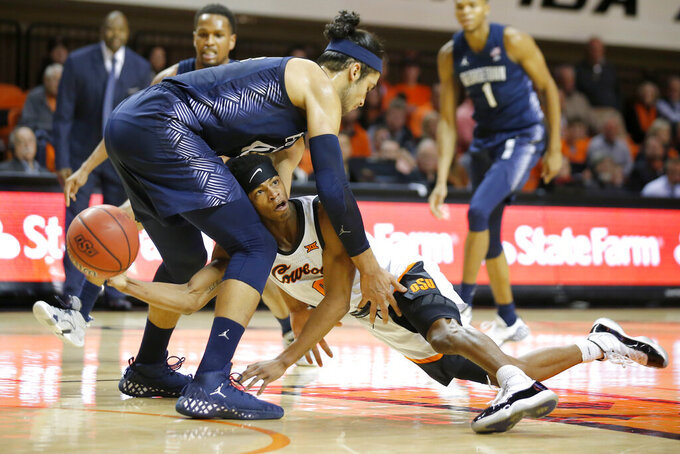 Oklahoma State's Avery Anderson III (0) tries to pass the ball from under Georgetown's Omer Yurtseven (44) during an NCAA college basketball game Wednesday, Dec. 4, 2019, in Stillwater, Okla. (Bryan Terry/The Oklahoman via AP)