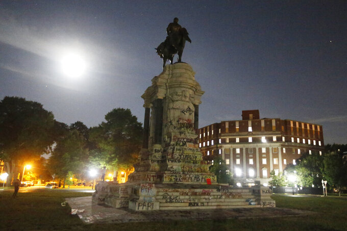 The moon illuminates the statue of Confederate General Robert E. Lee on Monument Avenue Friday June. 5, 2020, in Richmond, Va. The Supreme Court of Virginia ruled Thursday, Sept 2, 2021 that the state can take down an enormous statue that has towered over Monument Avenue in the state's capital for more than a century and has become a symbol of racial injustice. (AP Photo/Steve Helber, file)