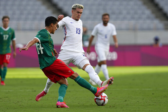 Mexico's Erick Aguirre, left, battles France's Clement Michelin for the ball during a men's soccer match at the 2020 Summer Olympics, Thursday, July 22, 2021, in Tokyo, Japan. (AP Photo/Shuji Kajiyama)