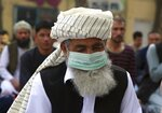 An Afghan Muslim man wearing a face mask as a precaution against coronavirus offers Eid al-Adha prayers in Kabul, Afghanistan, Friday, July 31, 2020. Muslims worldwide marked the the Eid al-Adha holiday over the past days amid a global pandemic that has impacted nearly every aspect of this year's celebrations. (AP Photo/Rahmat Gul)