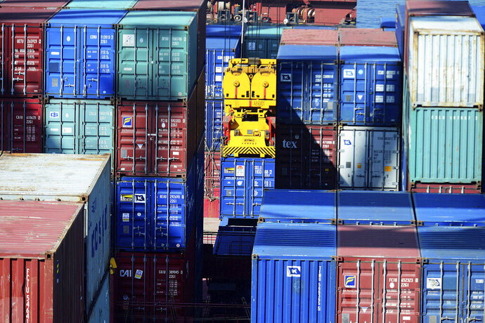 In this Thursday, May 23, 2019, photo, a crane lifts a shipping container at a port in Qingdao in eastern China's Shandong province. Stepping up a propaganda offensive against Washington, China's state media on Friday accused the U.S. of seeking to