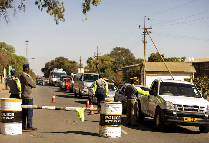 Police man a roadblock in Bulawayo, Zimbabwe, Monday, Aug. 19, 2019.  Few people turned up for an opposition protest Monday in the Zimbabwe's second city as armed police maintained a heavy presence on the streets. (AP Photo/Mpofu)