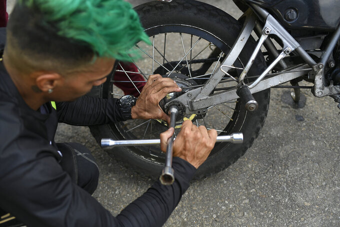 Motorcycle stuntman Pedro Aldana fixes his brakes during an exhibition in the Ojo de Agua neighborhood of Caracas, Venezuela, Sunday, Jan. 10, 2021. The 33-year-old makes a living with his shows, inspiring his young fans who flock to his shop, where he teaches them to change the oil and tune up their bicycles. (AP Photo/Matias Delacroix)