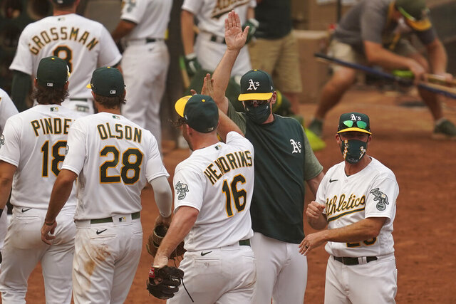 Oakland Athletics pitcher Liam Hendriks (16) celebrates with manager Bob Melvin, center right, after the Athletics defeated the Chicago White Sox 6-4 in Game 3 of an American League wild-card baseball series Thursday, Oct. 1, 2020, in Oakland, Calif. (AP Photo/Eric Risberg)