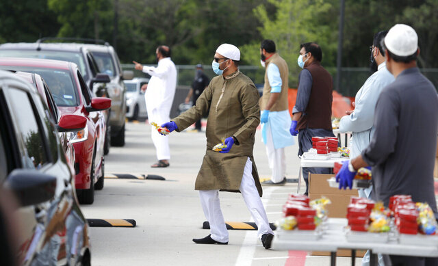 Organizers hand out treats during a drive through Eid al-Fitr celebration outside a closed mosque in Plano, Texas, Sunday, May 24, 2020. Many Muslims in America are navigating balancing religious and social rituals with concerns over the virus as they look for ways to capture the Eid spirit this weekend. (AP Photo/LM Otero)