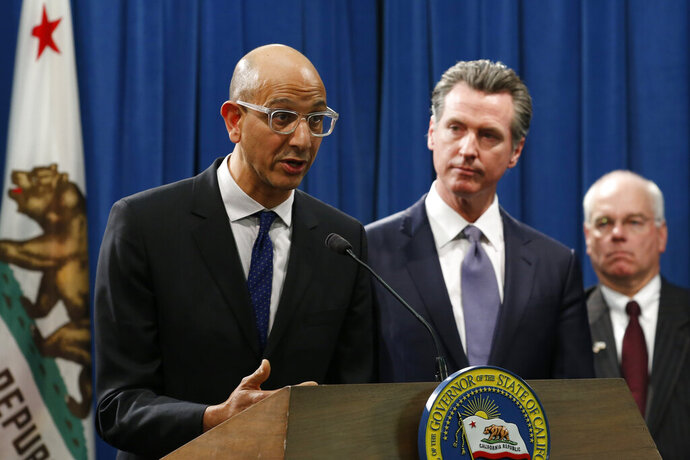 FILE - In this March 12, 2020, file photo Dr. Mark Ghaly, secretary of the California Health and Human Services, discusses the coronavirus as Gov. Gavin Newsom, center, listens at a news conference in Sacramento, Calif. Sacramento area officials were caught off guard when the state public health agency lifted the regional stay-at-home order, allowing businesses like barber and beauty shops and nail salons, to reopen, restaurants to offer outdoor dining, and houses of worship to offer outdoor services. (AP Photo/Rich Pedroncelli, File)