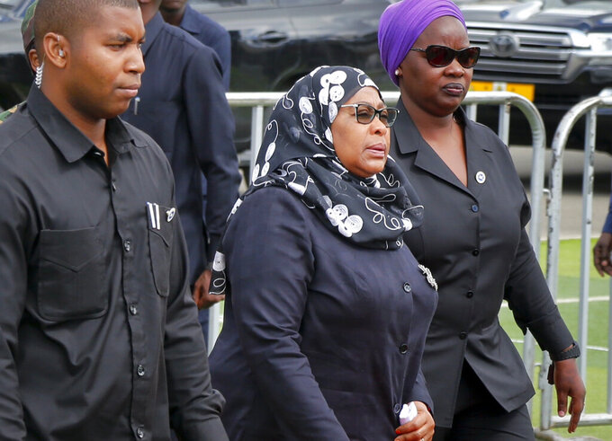 Tanzania's new President Samia Suluhu Hassan, center, arrives to pay her respects as the body of former president John Magufuli lies in state at Uhuru stadium in Dar es Salaam, Tanzania Saturday, March 20, 2021. Magufuli, a prominent COVID-19 skeptic whose populist rule often cast his country in a harsh international spotlight, died Wednesday aged 61 of heart failure, it was announced by Vice President Samia Suluhu Hassan, who was sworn-in as the country's new president on Friday. (AP Photo)