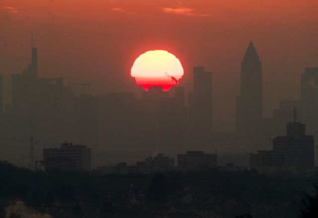 The sun rises behind the buildings of the banking district in Frankfurt, Germany, on a cold Saturday, Feb. 8, 2020. (AP Photo/Michael Probst)