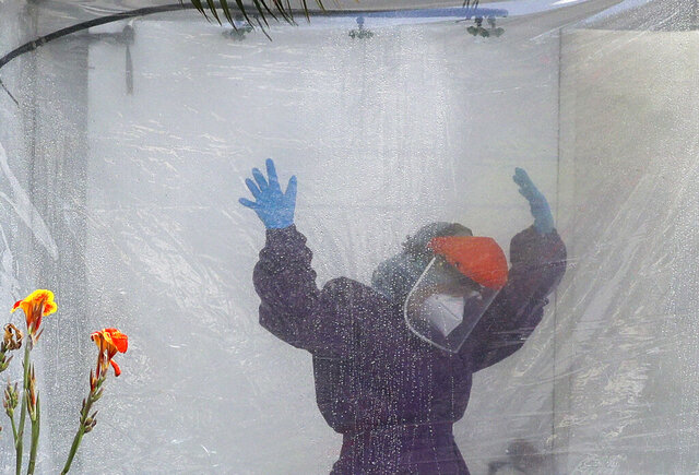 A health worker wearing a protective suit is disinfected inside a portable tent outisee the Gat Andres Bonifacio Memorial Medical Center during an enhanced community quarantine to prevent the spread of the new coronavirus in Manila, Philippines, Monday April 27, 2020. (AP Photo/Aaron Favila)