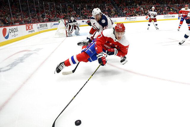Washington Capitals right wing T.J. Oshie (77) is tripped by Columbus Blue Jackets defenseman Dean Kukan, back, during the second period of an NHL hockey game Friday, Dec. 27, 2019, in Washington. (AP Photo/Nick Wass)