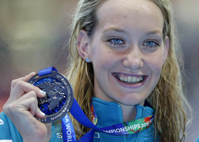 """FILE - Australia's Madison Wilson holds her silver medal after her second place finish in the women's 100m backstroke final at the Swimming World Championships in Kazan, Russia, in this Tuesday, Aug. 4, 2015, file photo. Olympic gold medal swimmer Madison Wilson of Australia has been hospitalized for treatment of COVID-19. Wilson, who is fully vaccinated, was forced to withdraw from the International Swim League competition in Naples, Italy because of the diagnosis. """"I'm taking some time to rest and I'm sure I'll be ready to bounce back in no time,"""" Wilson said in a post Sunday, Sept. 19, 2021. (AP Photo/Michael Sohn, File)"""