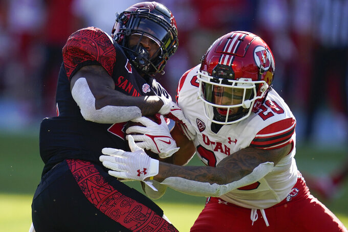 San Diego State running back Greg Bell (22) is tackled by Utah safety Brandon McKinney (28) during the first half of an NCAA college football game Saturday, Sept. 18, 2021, in Carson, Calif. (AP Photo/Ashley Landis)