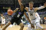 Washington forward Jayden McDaniels (0) attempts to spin around Hawaii forward Zigmars Raimo (14) during the second half of an NCAA college basketball game Monday, Dec. 23, 2019, in Honolulu. (AP Photo/Marco Garcia)