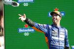 Mclaren driver Daniel Ricciardo of Australia throws his shoe as he celebrates after winning the Italian Formula One Grand Prix, at Monza racetrack, in Monza, Italy, Sunday, Sept.12, 2021. (AP Photo/Luca Bruno)