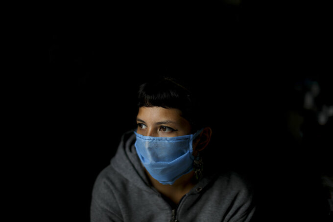 Volunteer Laura Da Costa, who helps prepare food, wears a protective face mask at a soup kitchen on the outskirts in Buenos Aires outskirts, Argentina, Wednesday, March 25, 2020. As a result of the new coronavirus pandemic, people are no longer allowed to eat at soup kitchen locations, but instead are asked to take the free meals to their homes in a plastic container. (AP Photo/Natacha Pisarenko)