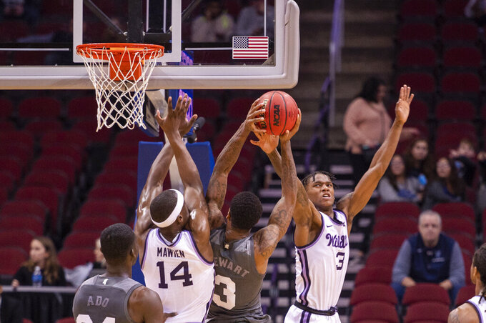 Kansas State forward Makol Mawien (14) and guard DaJuan Gordon (3) defend against Mississippi State guard D.J. Stewart Jr. (3) during the first half of the Never Forget Tribute Classic NCAA college basketball game, Saturday, Dec. 14, 2019, in Newark, N.J. (AP Photo/Corey Sipkin)