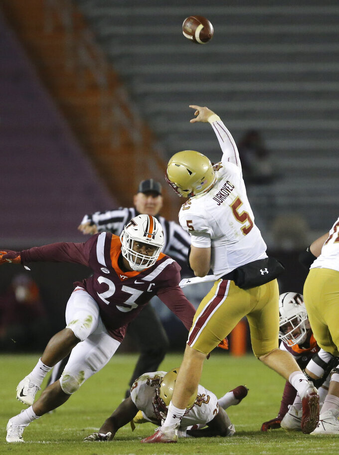 Boston College quarterback Phil Jurkovec (5) throws as he is rushed by Virginia Tech's Rayshard Ashby (23) in the fourth quarter of an NCAA college football game, Saturday, Oct. 17, 2020, in Blacksburg, Va. (Matt Gentry/The Roanoke Times via AP, Pool)