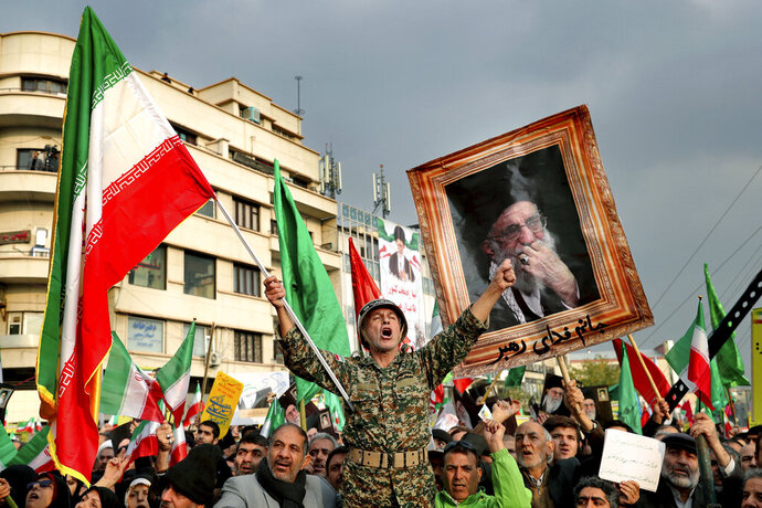 FILE - In a Nov. 25, 2019, file photo, a demonstrator chants slogans while holding up an Iranian national flag during a pro-government rally in Tehran, Iran, denouncing violent protests over a government-imposed fuel price hike. Even among hard-liners in Iran, there seems to be an acknowledgment of one fact after widespread protests, violence and a security force crackdown following government-set gasoline prices spiking: This will not be the last time demonstrators come out on the street. (AP Photo/Ebrahim Noroozi, File)