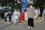 A protester holds a sign at Seoul National University Hospital where a funeral hall for late Seoul Mayor Park Won-soon was established in Seoul, South Korea. Friday, July 10, 2020. Park left a note saying he felt