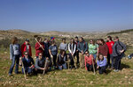In this Friday, Jan. 25, 2019 photo, American rabbinical students take a group photo,  with the village of Attuwani in the background, during a day planting olive trees, near Hebron in the West Bank. The students are doing more than visiting holy sites, learning Hebrew and poring over religious texts during their year abroad in Israel. In a departure from past programs that focused on strengthening ties with Israel and Judaism, the new crop of rabbinical students is also reaching out to the Palestinians. (AP Photo/Nasser Nasser)