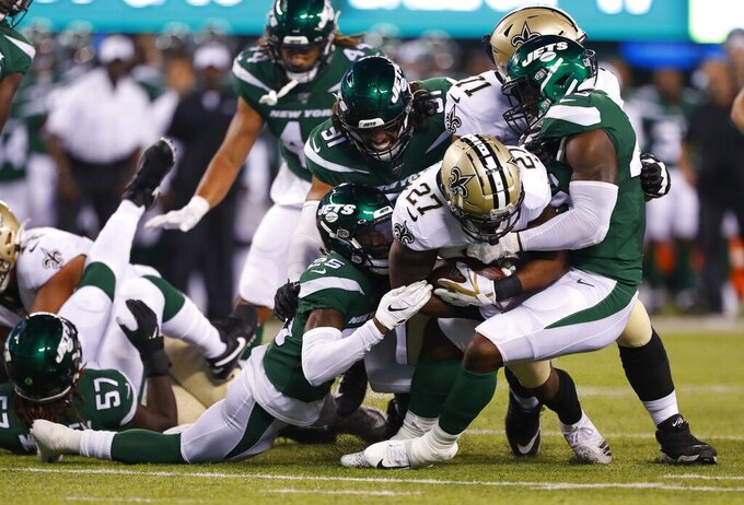 New Orleans Saints' Dwayne Washington (27) is tackled by New York Jets' Alex Brown (25), Neville Hewitt and Bronson Kaufusi (91) during the first half of a preseason NFL football game Saturday, Aug. 24, 2019, in East Rutherford, N.J. (AP Photo/Noah K. Murray)