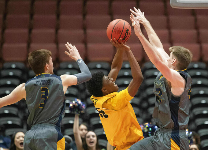 Long Beach State guard Deishuan Booker, center, shoots between UC Irvine guard Robert Cartwright, left, and forward Tommy Rutherford during the first half of an NCAA college basketball game at the Big West men's tournament in Anaheim, Calif., Friday, March 15, 2019. (AP Photo/Kyusung Gong)