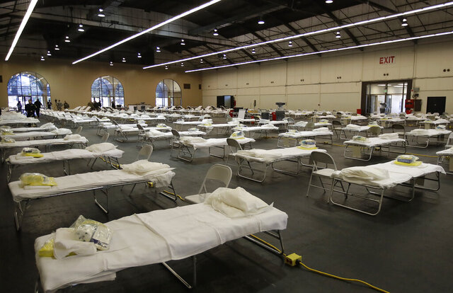FILE - In this April 1, 2020, file photo, cots are set up at a possible COVID-19 treatment site in San Mateo, Calif. With coronavirus cases rising fast, California is planning to keep open several makeshift hospitals that have seen few patients but cost a bundle, in one case more than $4 million to prepare and staff a facility that only treated two people over nearly two months. (AP Photo/Ben Margot, Pool, File)