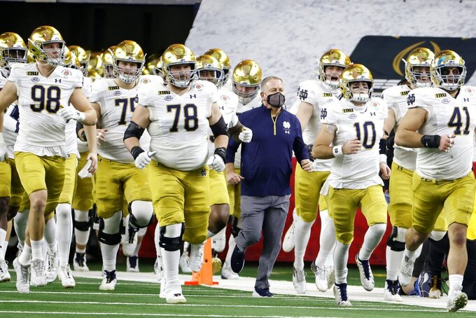Notre Dame head coach Brian Kelly, center, jogs onto the field alongside his team for at the start of the Rose Bowl NCAA college football game against Alabama in Arlington, Texas, Friday, Jan. 1, 2021. (AP Photo/Ron Jenkins)