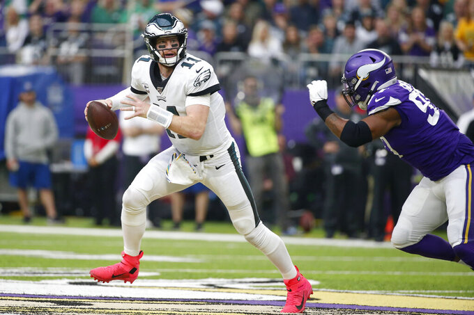Philadelphia Eagles quarterback Carson Wentz, left, runs form Minnesota Vikings defensive end Everson Griffen, right, during the first half of an NFL football game, Sunday, Oct. 13, 2019, in Minneapolis. (AP Photo/Bruce Kluckhohn)