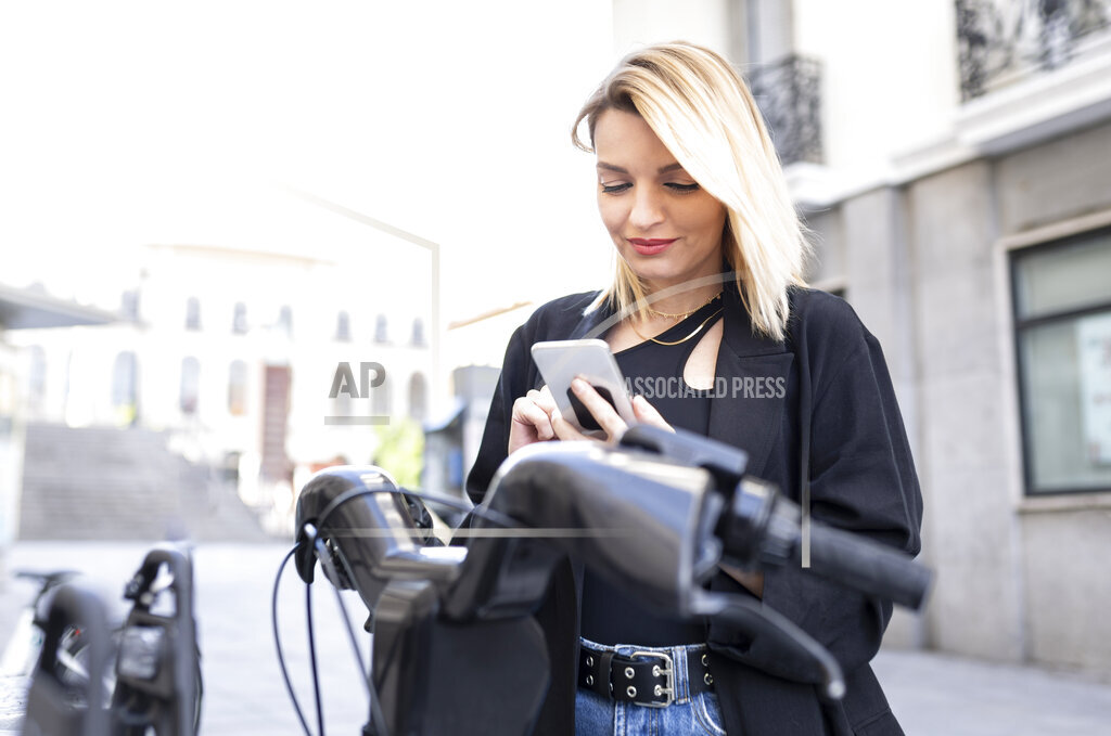 Beautiful woman using mobile phone in front of electric vehicle