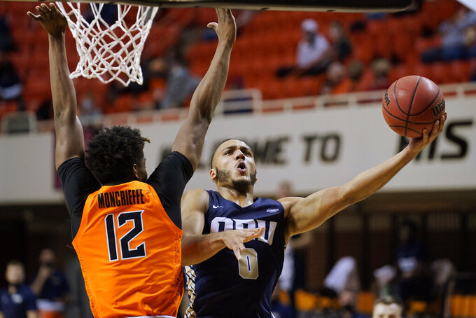 Oral Roberts forward Kevin Obanor (0) shoots as Oklahoma State forward Matthew-Alexander Moncrieffe (12) defends during the first half of an NCAA college basketball game Tuesday, Dec. 8, 2020, in Stillwater, Okla. (AP Photo/Sue Ogrocki)