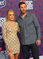 """FILE - In this June 5, 2019 file photo, singer Carrie Underwood, left, and Mike Fisher arrive at the CMT Music Awards in Nashville, Tenn. The couple's 5-year-old son provided the adorable vocals on """"Little Drummer Boy,"""" one of the 11 tracks on the country superstar's new Christmas album, """"My Gift,"""" out Friday, Sept. 25, 2020. (AP Photo/Sanford Myers, File)"""