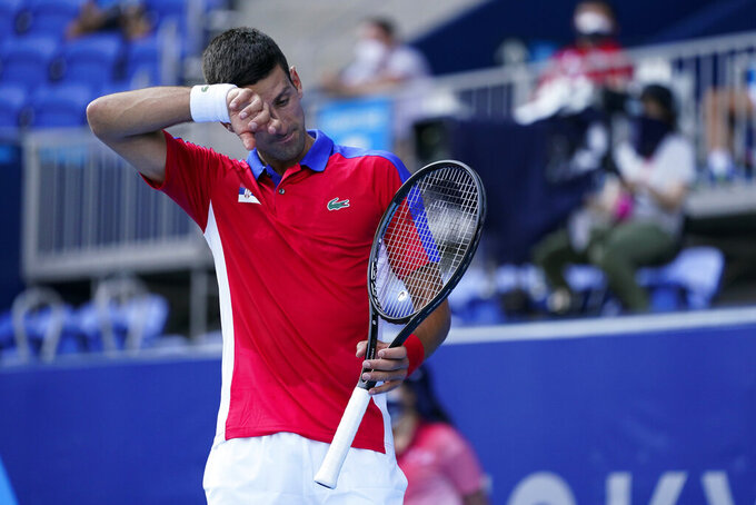 Novak Djokovic, of Serbia, wipes sweat from his brow as he competes Hugo Dellien, of Bolivia, during the tennis competition at the 2020 Summer Olympics, Saturday, July 24, 2021, in Tokyo, Japan. (AP Photo/Patrick Semansky)
