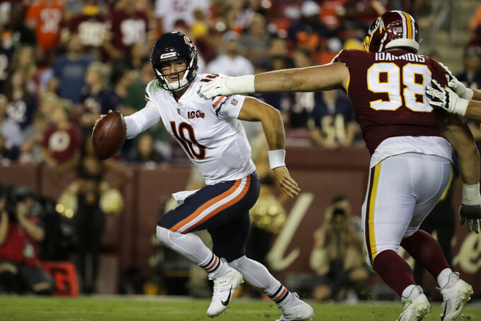 Chicago Bears quarterback Mitchell Trubisky (10) works to escape Washington Redskins defensive end Matthew Ioannidis (98) during the second half of an NFL football game Monday, Sept. 23, 2019, in Landover, Md. (AP Photo/Julio Cortez)