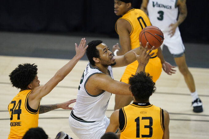 Cleveland State's Algevon Eichelberger (12) goes to the basket against Oakland's Jalen Moore (34) and Trey Townsend (13) during the first half of an NCAA college basketball game in the men's Horizon League conference tournament championship game, Tuesday, March 9, 2021, in Indianapolis. (AP Photo/Darron Cummings)